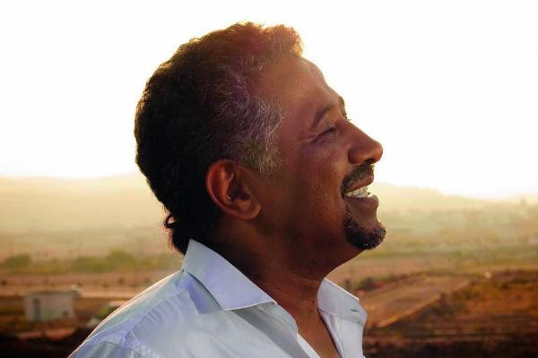 chanteur cheb khaled qui sourit et regarde au loin